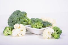 Grüner Brokkoli und Blumenkohl, die auf weißem Hintergrund liegt lizenzfreies stockbild
