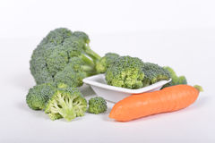 Grüner Brokkoli und Karotte, die auf weißem Hintergrund liegt Lizenzfreies Stockbild