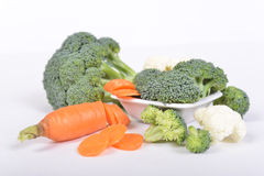 Grüner Brokkoli und Karotte schnitten in die piecies, die auf weißem Hintergrund liegen Stockfotografie