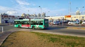 Grüner Bus geht entlang zentralen Busbahnhof Lizenzfreie Stockfotos