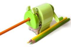 Grüner Drehbleistiftspitzer mit dem orange Bleistift lokalisiert auf whi Stockbild