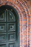 Grüner Eingang wölbte die Tür, die durch Ziegelsteinbogen des Gebäudes gestaltet wurde lizenzfreie stockbilder