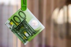 Grüner Euro der Banknote 100 im grünen Kleiderhaken Lizenzfreie Stockfotografie