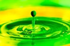 Grüner flüssiger Farbentropfen, der der gelben Farbe spritzt Stockfotografie