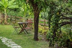 Grüner Garten der Küste mit Tabelle und Stühle an einem regnerischen Tag Stockfotografie