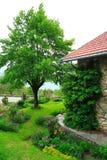 Grüner Garten und altes Haus Stockbilder