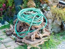 Grüner Gartenschlauch auf dem hölzernen Stapel Lizenzfreie Stockfotos