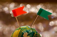 Grüner gelber Ball und zwei Plastikstiftflaggen Lizenzfreie Stockfotografie