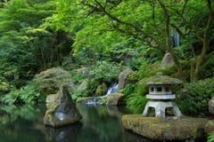 Grüner gemütlicher Garten mit einem kleinen Wasserfall stockfotografie