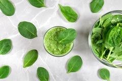 Grüner gesunder Smoothie und eine Schüssel frischer Spinat umgeben mit Spinatsblättern stockfotografie