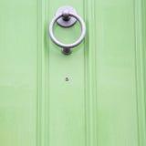 grüner Griff im rostigen Messingnagel antiker brauner Tür Londons Stockfotos