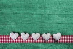 Grüner hölzerner Hintergrund mit Herzen auf einem roten Weiß überprüfte Rahmen Stockbilder