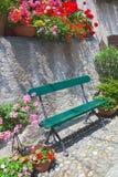 Grüner hölzerner Sitz in den roten, rosa Blumen und in den Anlagen Lizenzfreie Stockfotografie