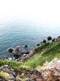 Grüner Hügel durch das Meer Lizenzfreies Stockfoto