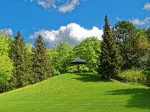 Grüner Hügel mit Bank unter Sonnenregenschirm im Park Lizenzfreie Stockfotos
