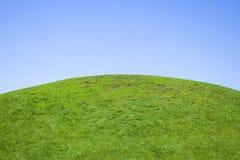 Grüner Hügel und blauer Himmel Stockfotos