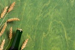 Grüner Hintergrund mit Bierflasche und den Ohren des Weizens stockfoto