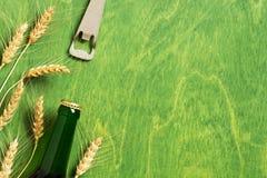 Grüner Hintergrund mit den Bierflasche, Öffner und Ohren des Weizens stockbild