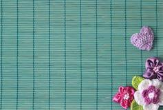 Grüner Hintergrund mit Häkelarbeitblume und -herzen stockbild