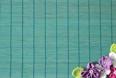 Grüner Hintergrund mit Häkelarbeitblume und -herzen lizenzfreies stockbild