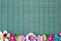 Grüner Hintergrund mit Häkelarbeitblume und -herzen stockfotos