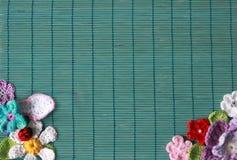 Grüner Hintergrund mit Häkelarbeitblumen stockbilder