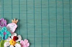 Grüner Hintergrund mit Häkelarbeitblumen und -vogel stockbild