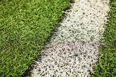 Grüner künstlicher Grasfußballplatz Der grüne Hintergrund stockbild