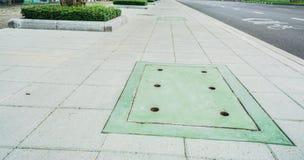 Grüner Kanaldeckel auf konkretem Fußweg Lizenzfreie Stockfotos