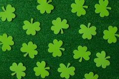 Grüner Klee oder Shamrocks auf grünem Hintergrund Stockfotografie
