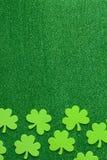 Grüner Klee oder Shamrocks auf grünem Hintergrund Lizenzfreie Stockfotos