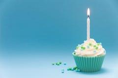 Grüner kleiner Kuchen mit Kerze und blauem Hintergrund Stockbild
