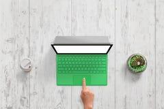 Grüner Laptop mit Weiß lokalisierte Schirm auf weißem hölzernem Schreibtisch Draufsichtszene Stockfotos