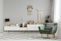 Grüner Lehnsessel auf kopiertem Teppich in hellem Wohnzimmer interio lizenzfreie stockbilder