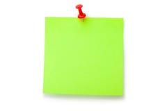 Grüner Leuchtstoffaufkleber auf rotem Thumbtack Stockfotos