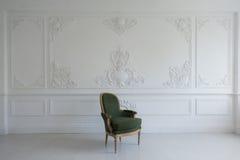 Grüner Luxuslehnsessel der Weinlese im Reinraum über Wandgestaltungsflachreliefstuckformteile roccoco Elementen Stockfotografie