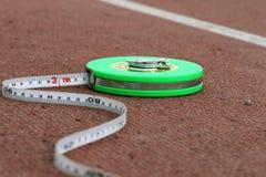Grüner Maßband, der auf einem roten Laufbahnstadion liegt Lizenzfreie Stockbilder