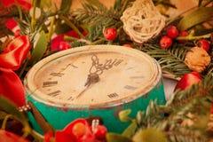 Grüner Mistelzweig und alte Uhr Stockbild