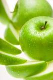 Grüner nasser Apfel mit Scheiben auf weißem Hintergrund Lizenzfreie Stockbilder