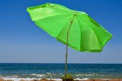 Grüner Neonregenschirm auf dem Strand, der den blauen Ozean im Sommer übersieht Lizenzfreie Stockfotos