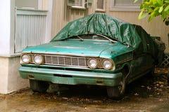 Grüner Oldtimer geschützt vor dem Regen und dem Laub Lizenzfreie Stockfotos