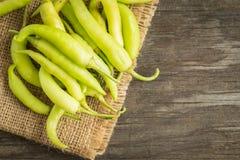 Grüner Paprika auf Sackleinen auf altem hölzernem Hintergrund Stockfoto