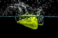 Grüner Paprika, der Wasser spritzen lässt stockfoto