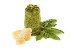 Grüner Pesto im Glas mit Stück des Käses und des Blattes des Basilikums Lizenzfreie Stockfotografie