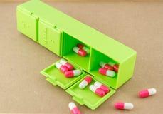 Grüner Pillenkasten mit Pillen im Kasten auf hölzernem Hintergrund Stockbilder