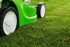 Grüner Rasenmäher auf grünem Rasen. Lizenzfreie Stockbilder