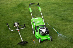 Grüner Rasenmäher, Unkrauttrimmer, Rührstange und Baumschere auf dem Rasen Stockfoto