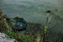 Grüner Regenschirm, der in den Fluss schwimmt Stockbild