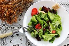 Grüner Salat mit Erdbeerstücken Stockbild