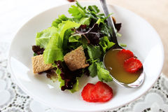 Grüner Salat mit Erdbeerstücken Stockfoto